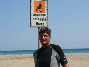 Fernando Trotto sotto il cartello che indica l'accesso alla spiaggia per i disabili, ma in realtà è scomparsa la passerella