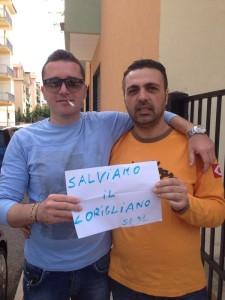 """Due tifosi del Corigliano calcio espongono un foglio con la scritta """"Salviamo il Corigliano"""""""